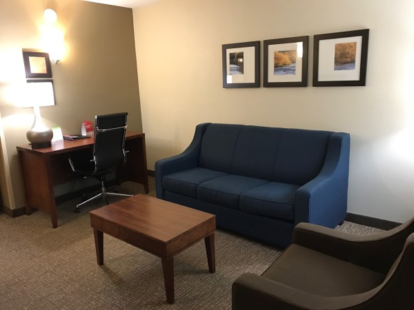 The front living area in the Comfort Suites room is spacious and includes couch, sitting chair, tv, and computer desk.