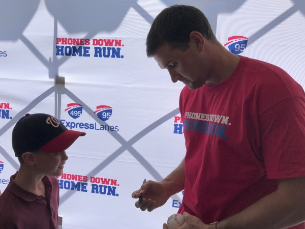 Ryan Zimmerman signs baseball during Phones Down Home Run safety campaign launch in McLean VA